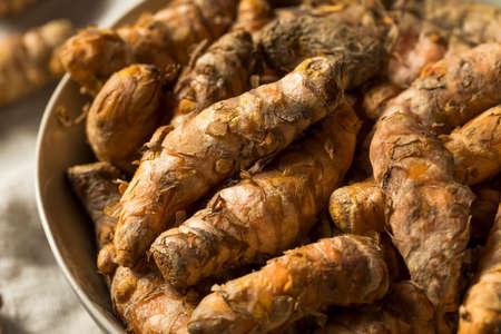 Raw Organic Orange Turmeric Root in a Bowl Stock Photo
