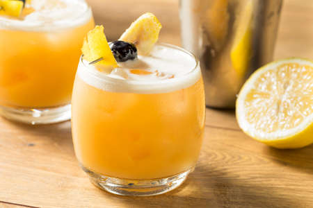 Sweet Homemade Whiskey Amarreto Sour Cocktail with a Cherry Stock Photo