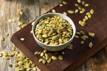 Pepitas de semillas de calabaza orgánicas verdes crudas en un tazón