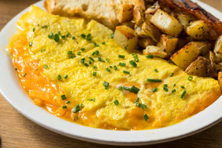 Homemade Healthy Cheese Omelet for Breakfast with Potatoes and Bacon