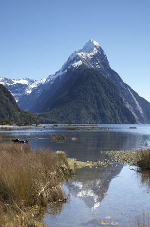 Mitre peak, New-Zealand at Milford Sound with a reflection in the lake. photo