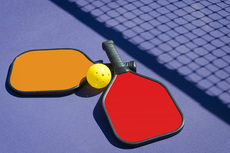 yellow ball: Pickleball - Two paddles and a ball in Net Shadow Stock Photo
