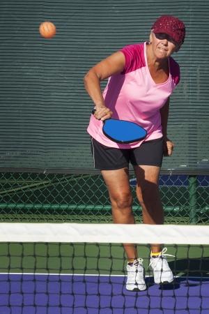 striking: Pickleball Action - Senior Woman Striking Ball