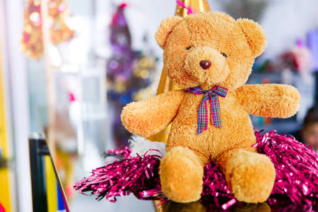 The brown teddy bear is sitting in a party celebrating