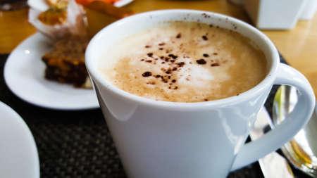 Een kopje cappuccino koffie met schuim en chocolade bovenop op houten tafel achtergrond. het is een witte keramische kop in het ochtendontbijt
