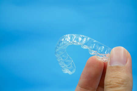 hand holding clear plastic retainer teeth that isolated on blue sky background. it's an equipment for orthodontist give the patient to orthodontic surgery in dental clinic or hospital Stock Photo