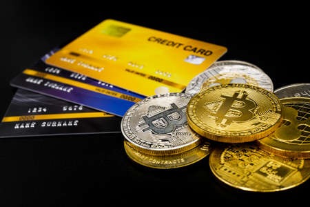 physical version of bitcoin and leather wallet and credit card  that is a new virtual money world cryptocurrency and digital payment system by using blockchain technology on black background
