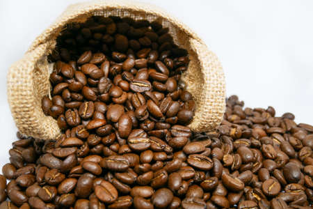 cup of coffee and coffee beans in a vintage sack on isolated white background, top view