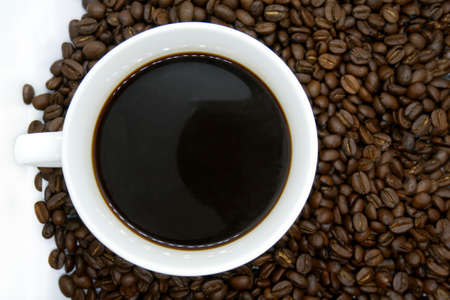 white coffee cup and roasted coffee beans that isolated on white background. top view.