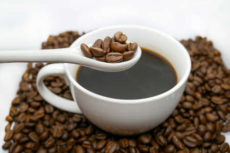 white coffee cup, spoon and roasted coffee beans that isolated on white background. top view.