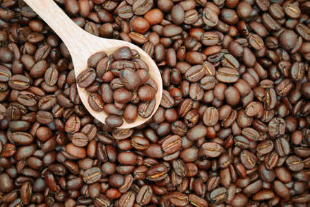 Many brown roasted coffee beans and wood spoon texture background