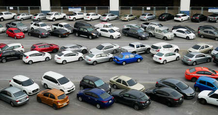 Cars parked in outdoor parking lot at with many of buildings in background.