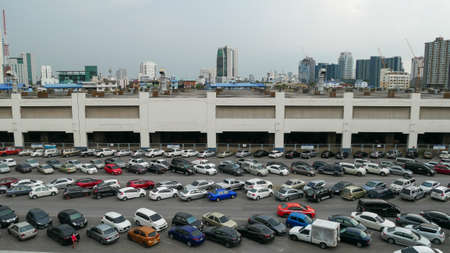Bangkok, Thailand - May 23, 2020: Cars parked in outdoor parking lot at Mo Chit BTS station with many of buildings in background. Panorama view.