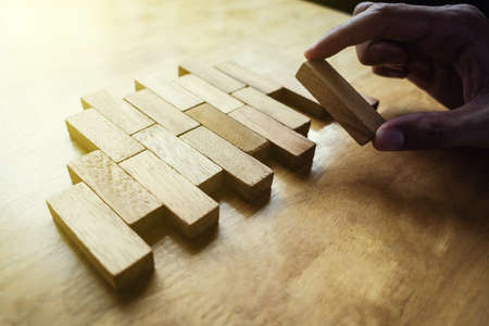 The way planning for business growth with wooden blocks, hand of  man is putting wooden block finally piece, plan and strategy in business.