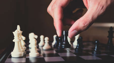 Hand of businessman making move with black rook on chess board, plan and strategy in business concept.