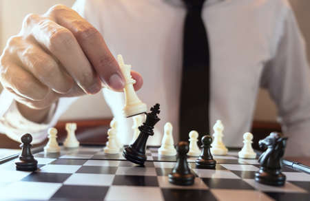 Closeup photo of businessman playing chess and beating black king,  plan and strategy in business concept.