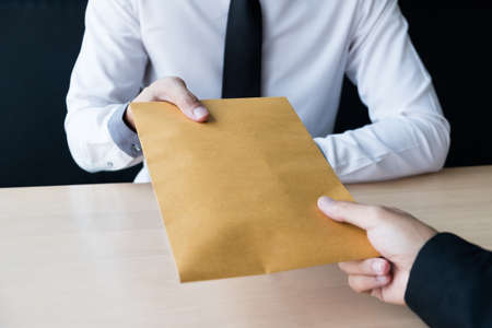 The businessman receiving bribe money in a brown envelope form another man at the office, Bribery and corruption concept.