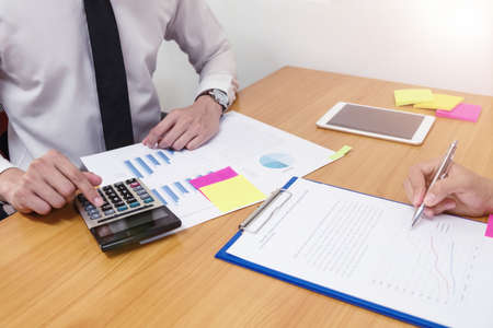 Business man is using a calculator to calculate the numbers with business woman on wood desk, business finances and accounting concept.