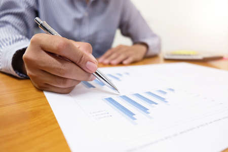 Businessman is using a pen for financial data analyzing counting on wood desk, business finances and accounting concept.