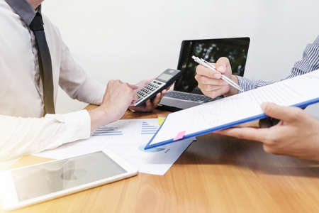 Businessman is calculating the budget that employee is offering and taking about work.