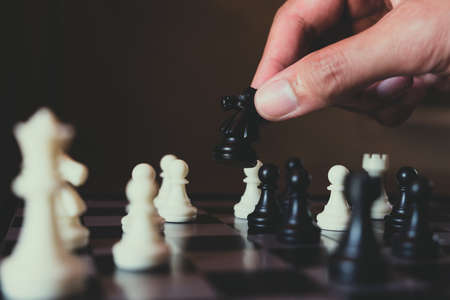 Hand of businessman making move with black knight on chess board, plan and strategy in business concept. Stock Photo