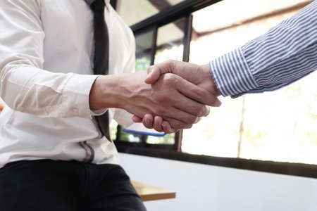 Close-up of two business people shaking hands, finishing up a meeting, business finances and accounting concept.