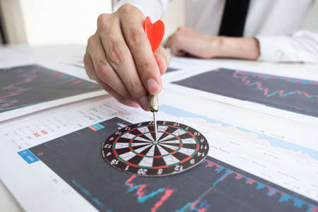 Businessman is holding a darts stick into the bullseye for make targeted of investment, Business and stock concept.