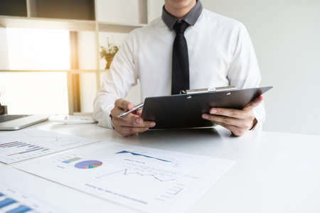Businessman is analyzing marketing strategy from the selling performance graph in the office room, Finance and accounting concept.