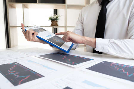 Businessman is analyzing stock graph for planning strategy of investment in the office room, Business and finance concept.