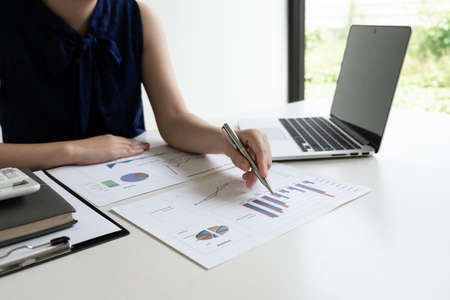 Business women is analyzing marketing strategy from the selling performance graph in the room and work from home, Finance and accounting concept.