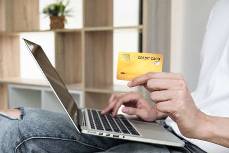 Closeup hand of a men is holding the credit card and using computer notebook for shopping online.