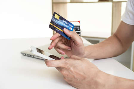 Closeup hand of a men is holding the credit card and using mobile phone for shopping online.