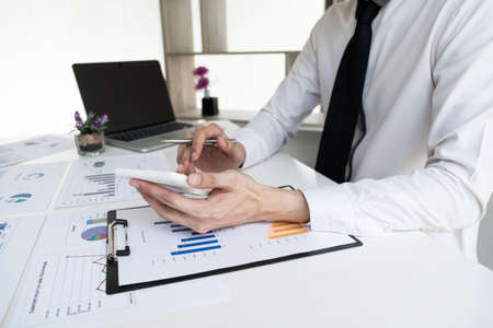 Businessman is calculating revenue from graph in the office room, Finance and accounting concept. Zdjęcie Seryjne