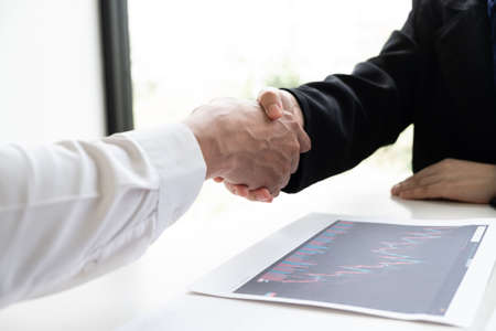 Two business people are shaking hand after concluding an agreement to put the buoy together.