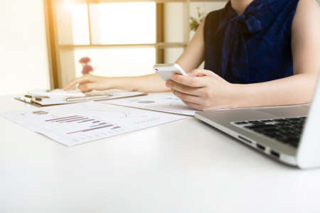 Business women is holding mobile phone and calculating revenue from graph in the office room, Finance and accounting concept.