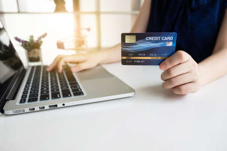 Closeup hand of women is holding a credit card and using computer notebook for shopping online.