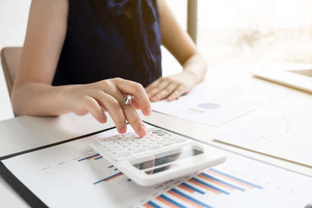 Business women is calculating revenue from graph in the room and work from home, Finance and accounting concept.