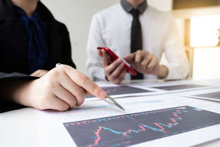 Two business people are discussing and analyze strategy of investment from the stock graph in the office room, Business and finance concept.