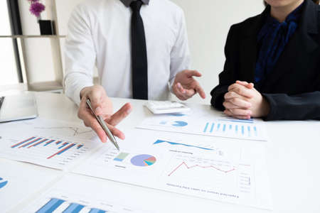 Two business people are discussing and analyze marketing strategy from the sell performance graph in the office room, Finance and accounting concept.