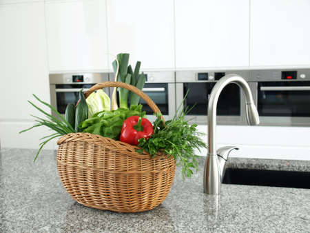 counter top: Wickerwork basket full of vegetables in a modern kitchen interior Stock Photo