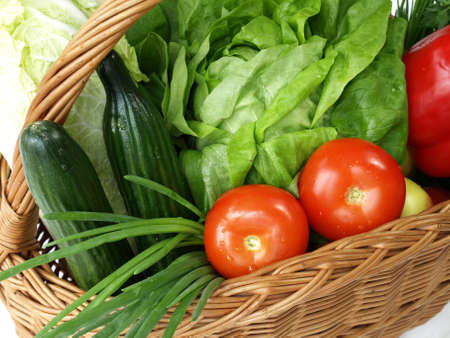 Basket with fresh, spring time vegetables on isolated background photo