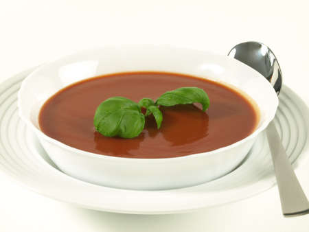 Closeup of tomato soup with basil in a white bowl photo
