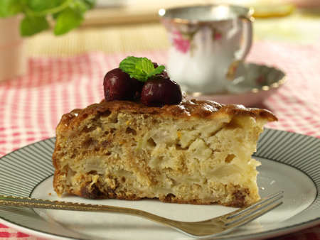 Piece of a sweet apple cake decorated with cherries and a cup of coffee in the background photo