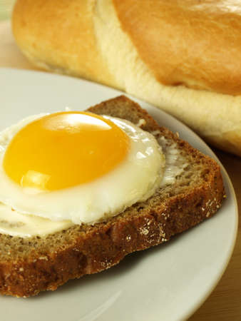 sunny side up: Sunny side up egg on a slice of bread on a plate with a French loaf in the background Stock Photo