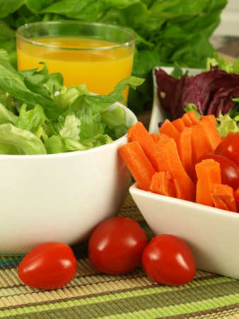 Carrot sticks, tomatoes and lettuce with orange juice for lunch photo