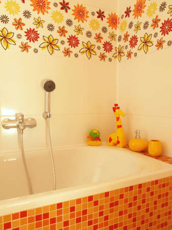 Closeup of a mosaic bath with a shower, yellow children toys and flower tiles photo
