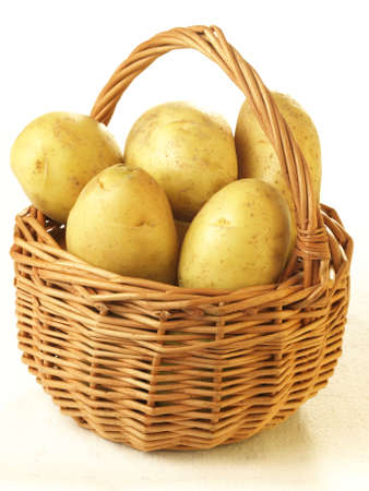 unpeeled: Unpeeled potatoes in basket on isolated background