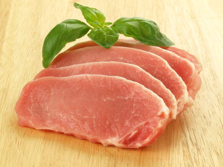 Slices of fresh pork decorated with basil leaves Stock Photo - 13150649