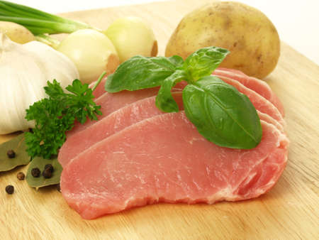 Slices of raw pork with herbs and vegatables photo