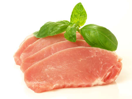 Slices of raw meat with basil leaves photo